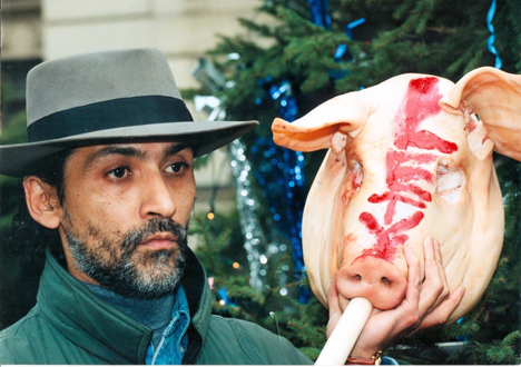 Lubo Zubak demonstrating at the Czech Prime Minister's office on 10 December 1997, hold a pig's head with the word LETY written in lipstick