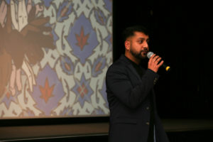 Riz giving speech at event