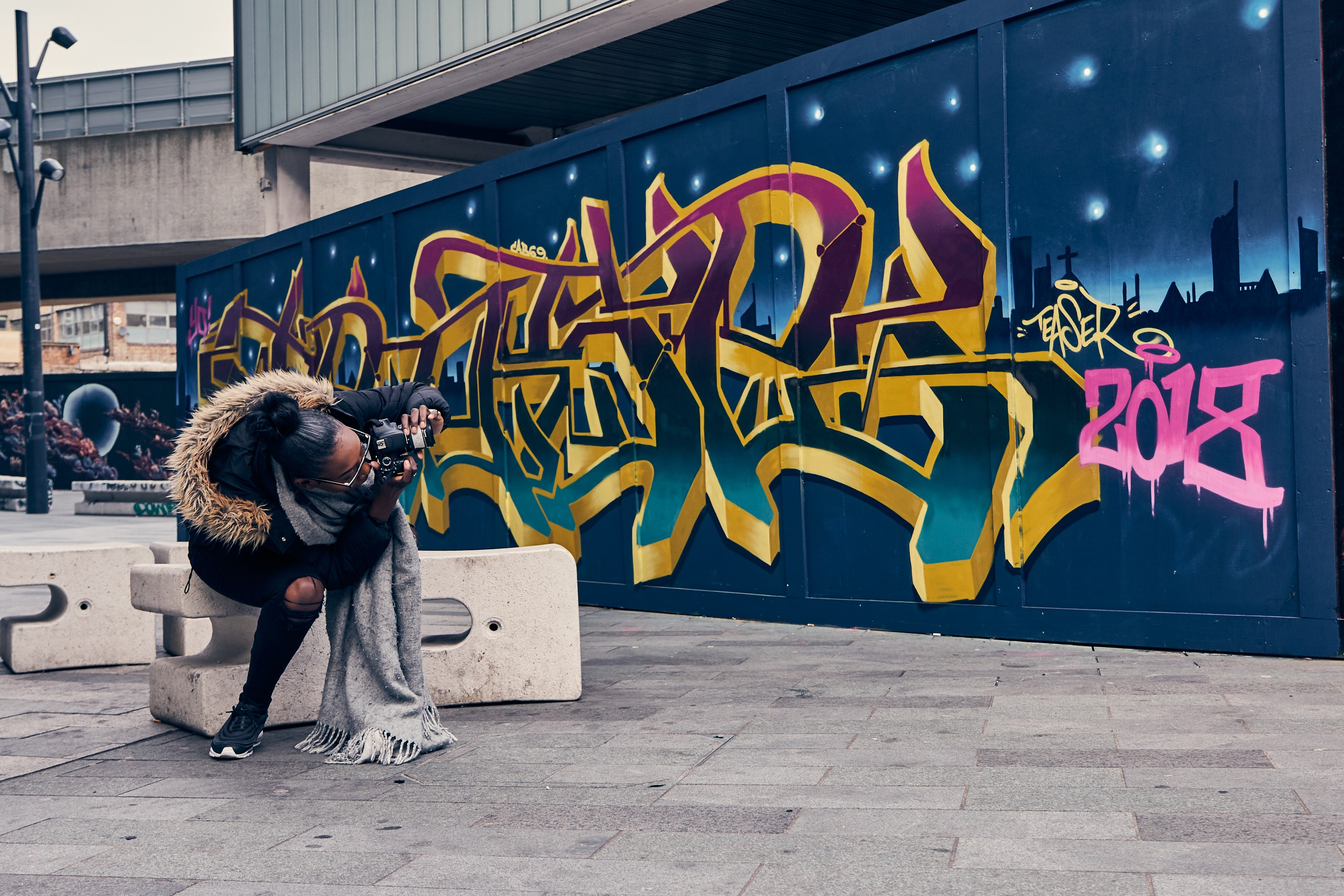 young woman taking photo of graffiti