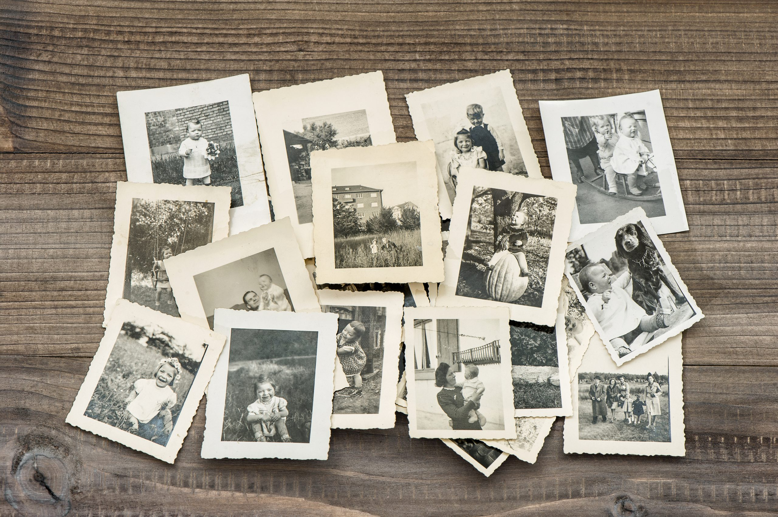 Old family photos on wooden table. Vintage pictures