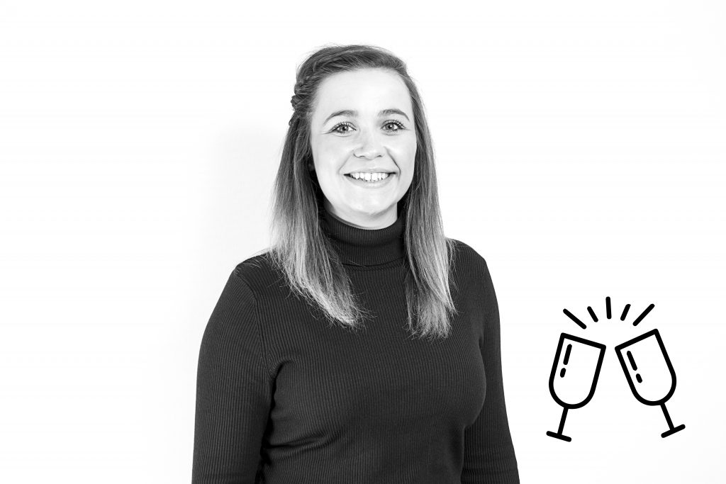 An image of Becca Tyler with prosecco glasses to celebrate her promotion