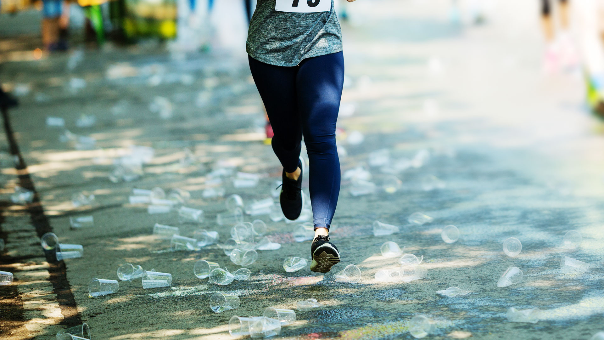 Runner running through road covered in plastic cups