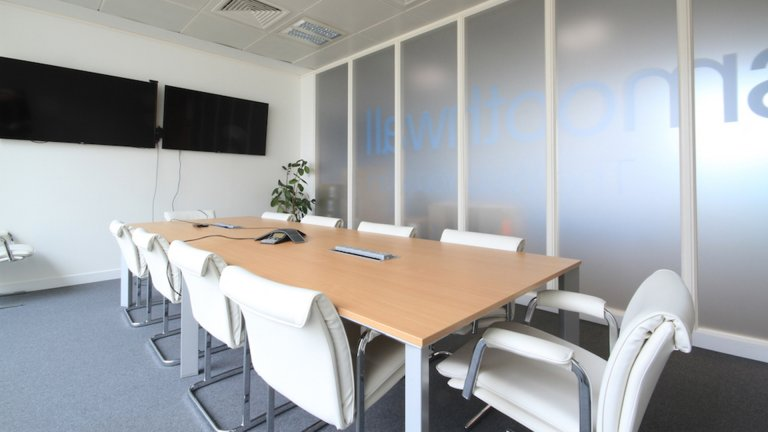 Boardroom table with white chairs