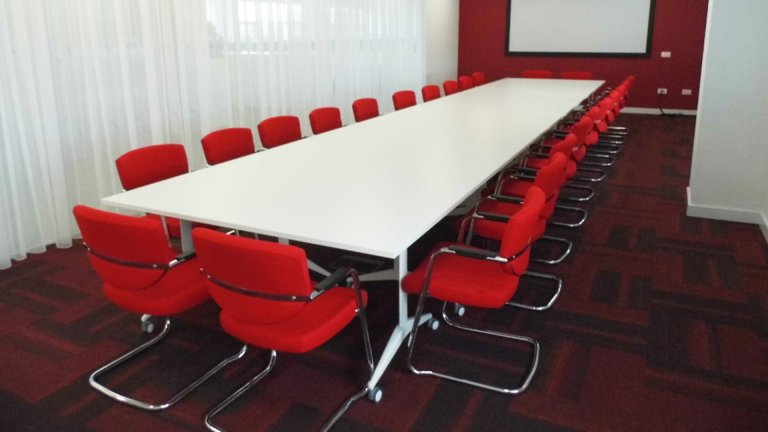 Boardroom table with red chairs