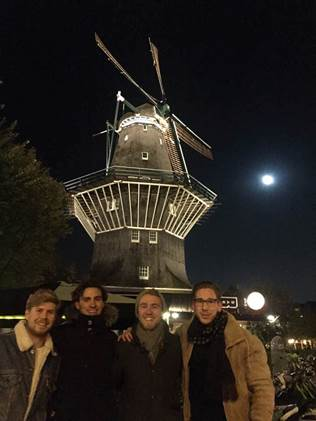 James Chowen and colleagues in front of a windmill at night