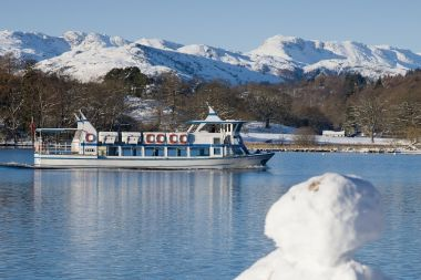 Miss Lakeland II travelling past a snowman on the shore