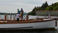 Two cyclists bringing bikes on board the Cross Lakes service.