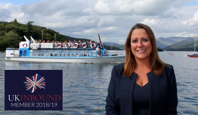 Jen Cormack on the Windermere shoreline with a launch (boat) behind her.