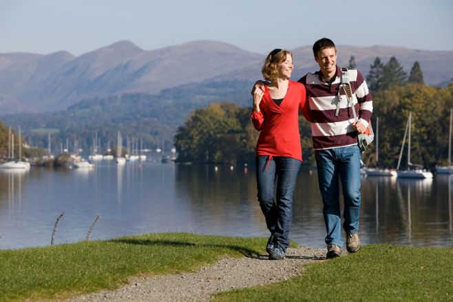 A couple walking along the shores of Lake Windermere