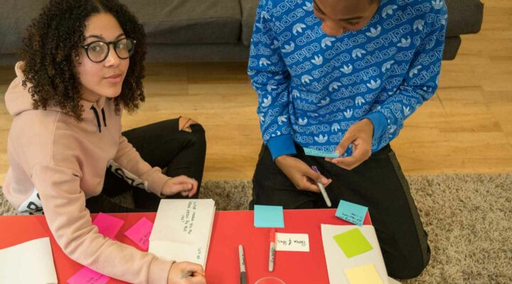 Young people using pens, paper and post-its to code sign a new service