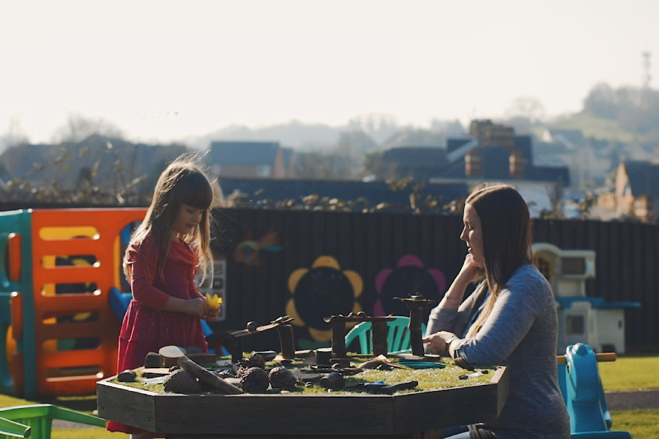 A little girl and her mum are in a garden, playing with toys at a table.