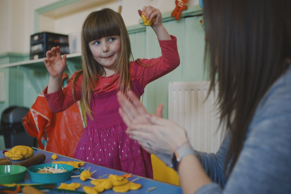 A little girl and her mum play with play dough and matchsticks. The little girl is standing up with her arms raised and wears a cheeky expression.