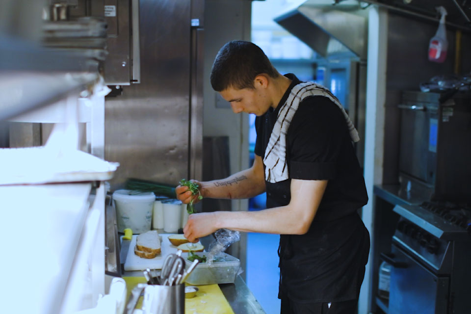 The same young man who was shown in the previous picture is working in a kitchen, handling salad leaves.