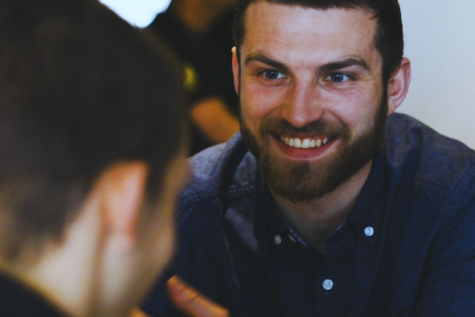 Close-up of a young man with a beard smiling at another man, who can just be seen in the foreground.