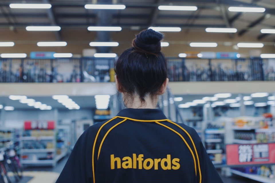 A back view of a woman wearing a Halfords uniform – a black polo shirt with 'Halfords' written on the back in orange.
