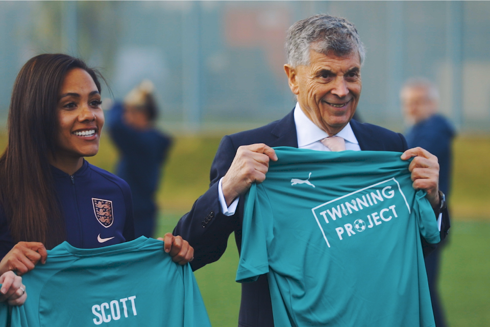Alex Scott and David Dein smile and hold up green Twinning Project t-shirts.