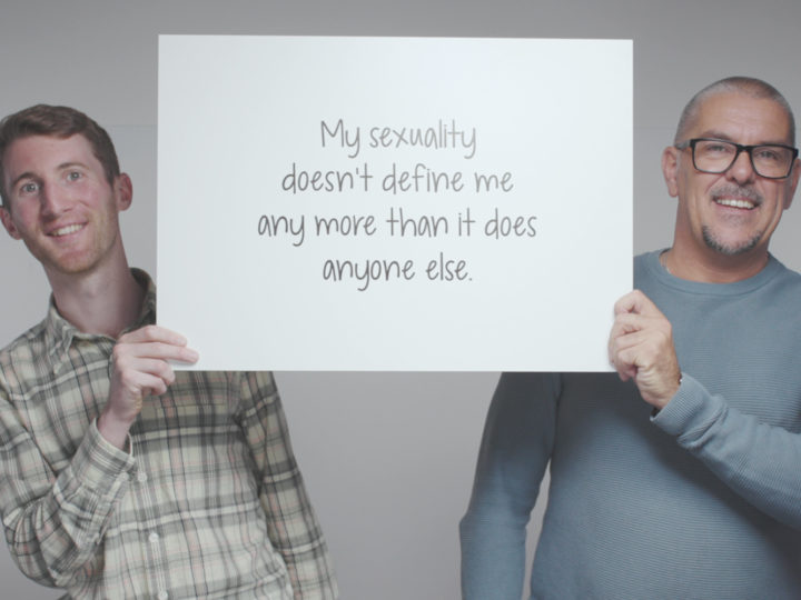 Two men smile into the camera and hold between them a banner reading 'My sexuality doesn't define me any more than it does anyone else.'