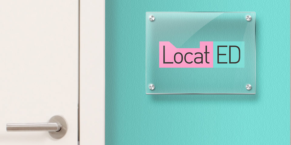 Pink and turquoise LocatED logo mocked up onto a small glass plaque on a turquoise office wall next to a white door.