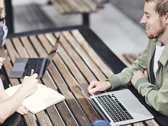 Three designers are having a meeting on a wooden picnic table. Only one of them is fully in shot; you can only see the arms of the other two. One designer is writing in a notebook and the other two have their laptops open.
