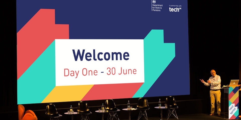 The Next Sprint branding on the opening slide of a presentation. It says 'Welcome, Day one - 20 June'. A man stood at a lectern presents to the audience.