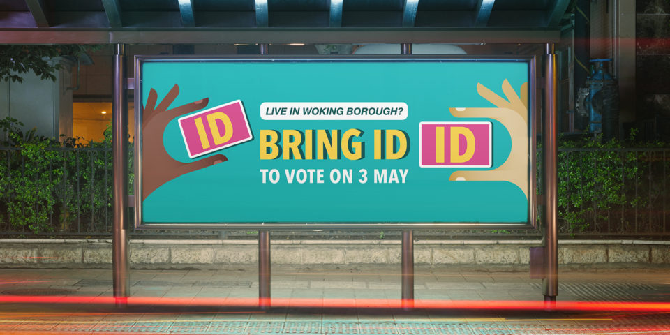 A mockup of a landscape billboard outdoors. It has graphic hands on each end, each holding a pink ID document with 'ID' on it. It's on a bright turquoise background. The writing on the billboard says 'Live in Woking borough? Bring ID to vote on 3 May'