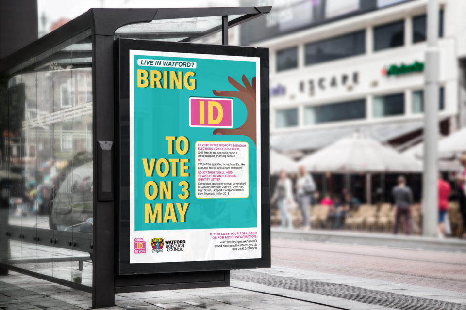 A mockup of a bus stop with Voter ID poster. It reads 'Live in Watford? Bring ID to vote on 3 May'.