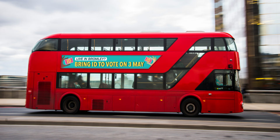 A mockup of the side of a moving red London bus with Voter ID graphic. It reads 'Live in Bromley? Bring ID to vote on 3 May.'