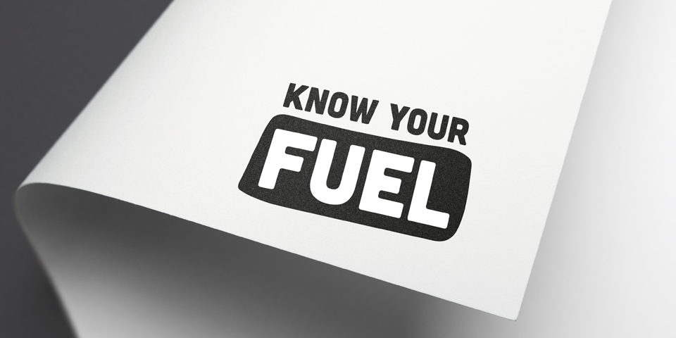 A close-up of the Know Your Fuel black and white logo mocked up on the corner of a piece of white paper.