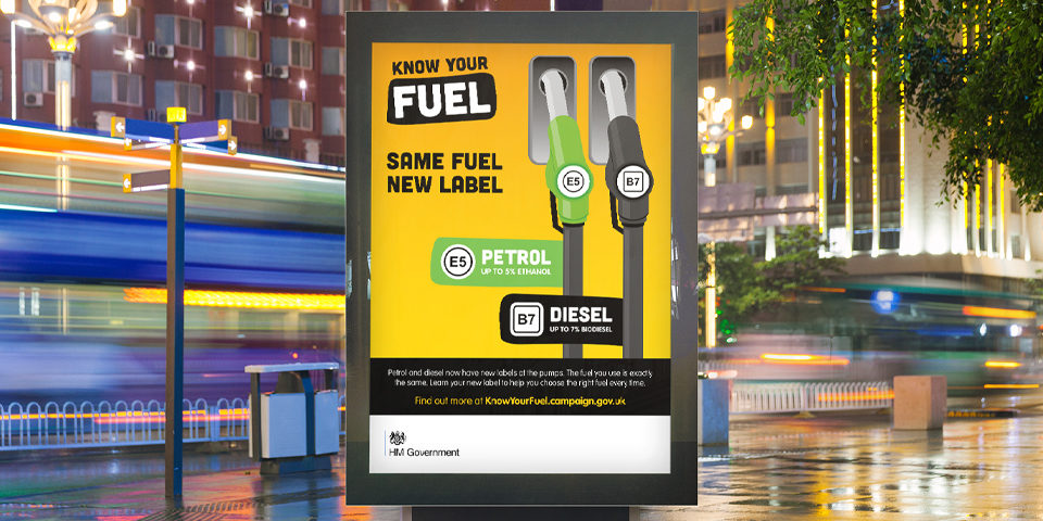A Know Your Fuel bus stop poster. It shows a green and a black fuel pump in a simple graphic style and the slogan 'Same fuel new label', on a yellow background.