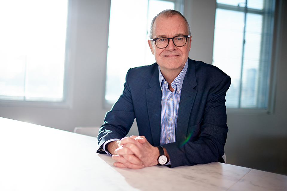 Dr Patrick Vallance, Chief Scientific Adviser to the government, sits at a table with his hands resting on top of it. He smiles directly into the camera.