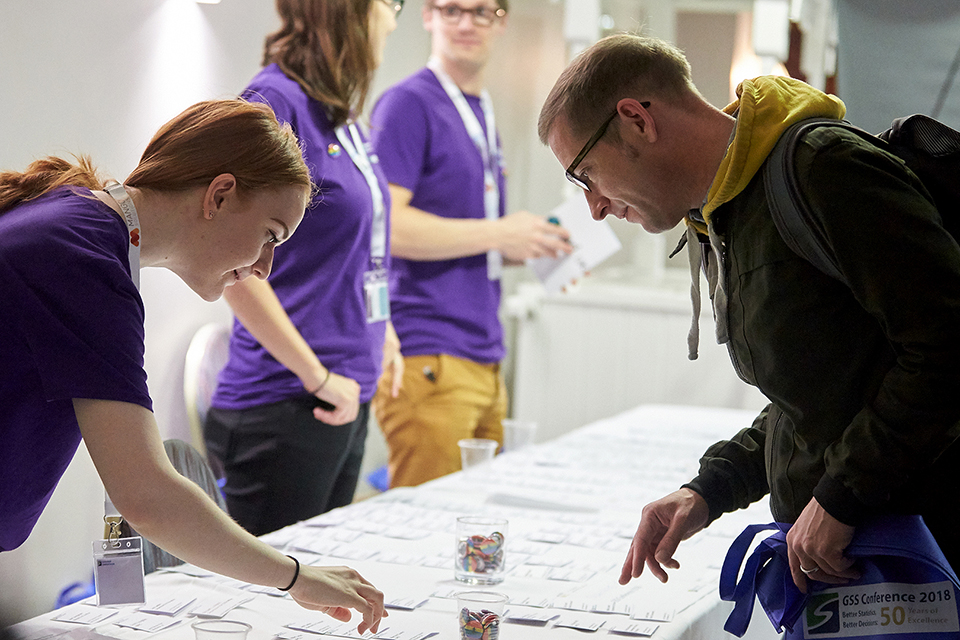 A woman working at the event helps an attendee find his name badge on a table.