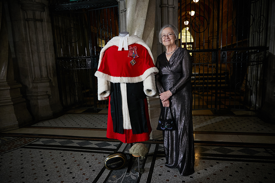 Baroness Hale stands, smiling, next to the judicial red robes and wig, in the grand setting of the Royal Courts of Justice.