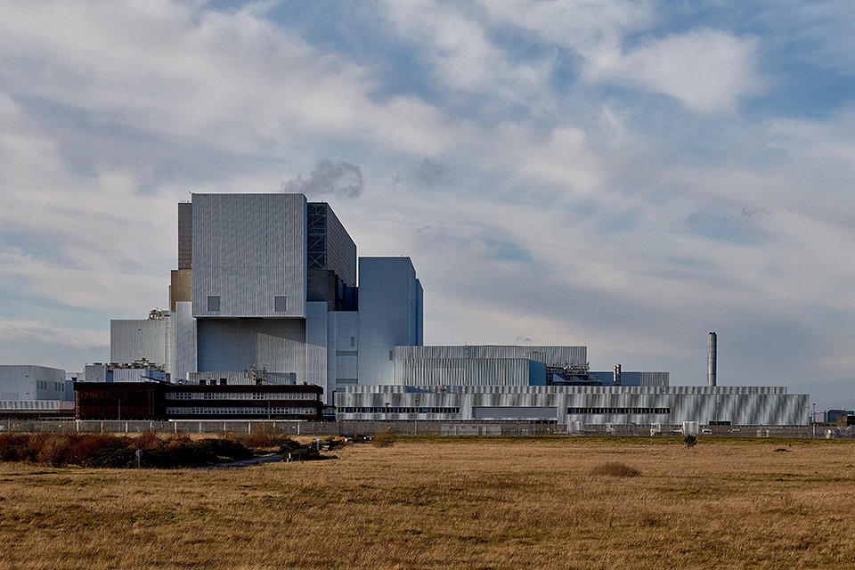 Landscape shot of the nuclear power station under a cloudy sky. The architecture is grey and angular and a field of light brown grass is in the foreground.