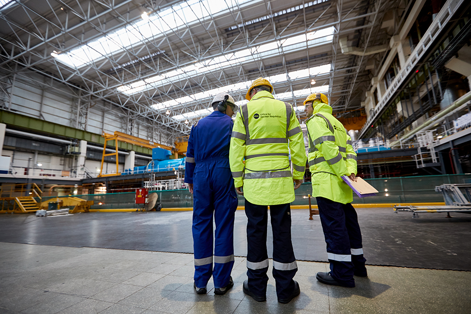 Three power station staff wearing hard hats and high vis jackets are talking inside the power station. The photograph is taken from behind.