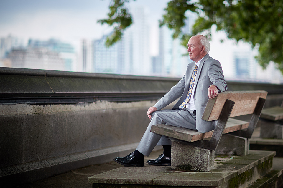 Peter Lawrence OBE sits on a bench in Westminster, looking towards the Thames. He is in focus but the buildings and tree in the background are blurred.