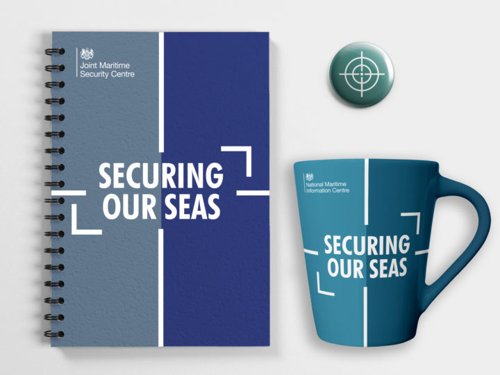 Mockups of a wire-bound notebook, mug and pin badge featuring the maritime branding. The notebook and mug have the words 'securing our seas' on them.