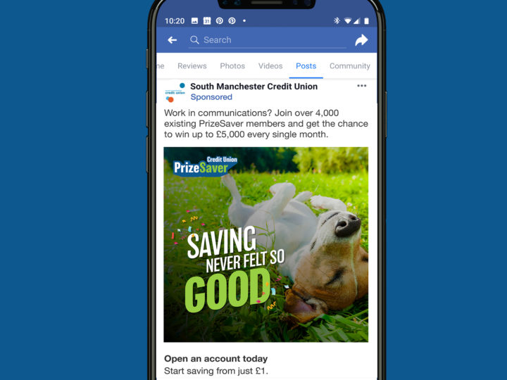 Smartphone mockup on a dark blue background picturing a Facebook advert. The advert shows a dog laying on its back on some grass with the wording 'Saving never felt so good'