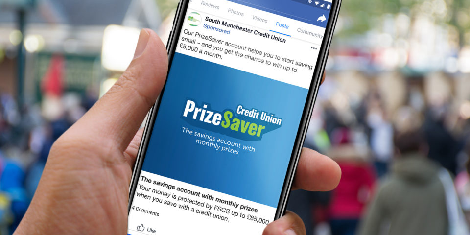 Hand holding up a smartphone with a mockup of a PrizeSaver Facebook post. The post shows the PrizeSaver logo on a blue background and the streamline 'the savings account with monthly prizes'