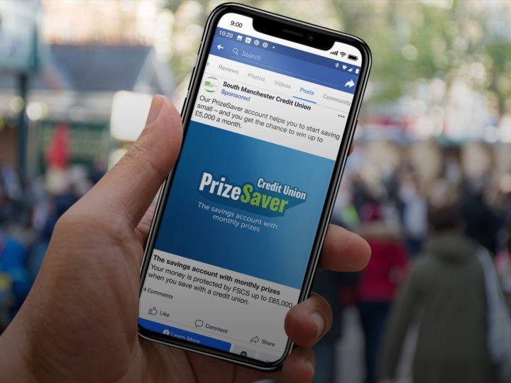 A hand holds a smart phone with the PrizeSave logo shown on what looks like somebody's Facebook feed.