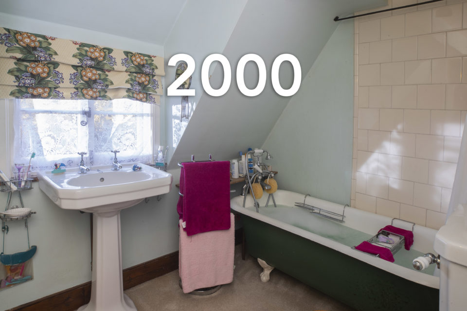 A family bathroom shows a free standing sink and bath full of water next to handing pink towels, the year 2000 is written over the photo