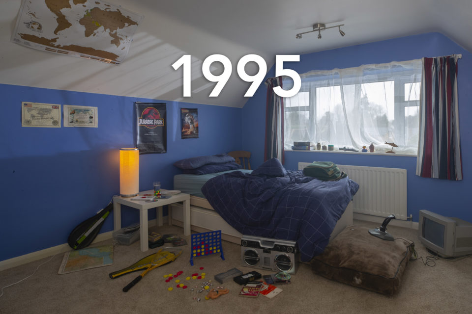 A classic 90s child's bedroom, toys surround an unmade bed and the walls are painted blue, the year 1995 is written over the photo