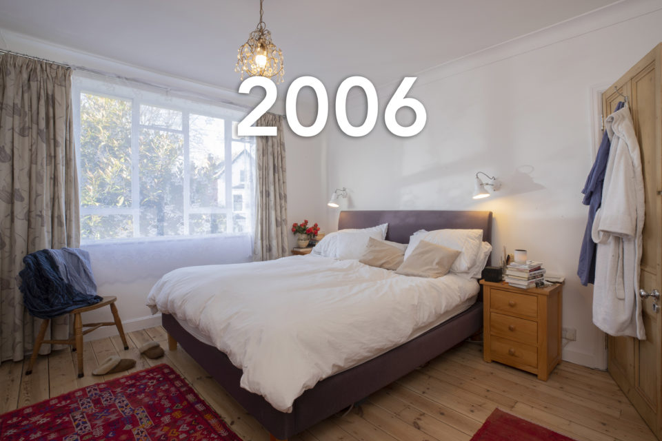 A double bed is in the centre of the room, someone's clothes have been thrown on the chair in the corner and bath robes hang off the door, the lights are on though sunshine is coming in through the window, the year 2006 is written over the photo