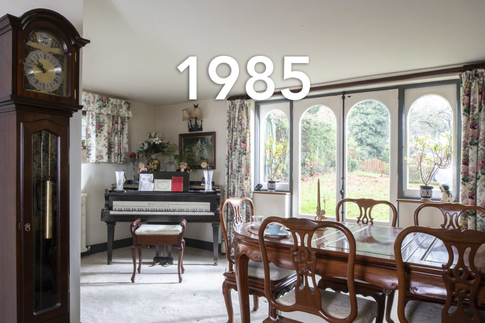 A bright dining room looks out over a garden, in the foreground a grandfather clock and a dining table surrounded by chairs, in the background card and a vase sit atop a piano, the date 1985 is written over the image.