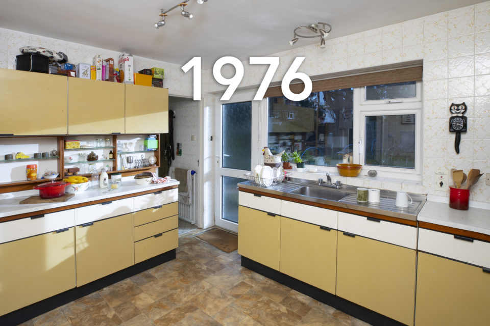 A typical 70s kitchen complete with yellow laminate cupboards and iconic, black, Kit-Cat Clock, glasses sit next to the sink and open boxes of cereal have been placed on top of the cupboards, the date 1976 is written over the image