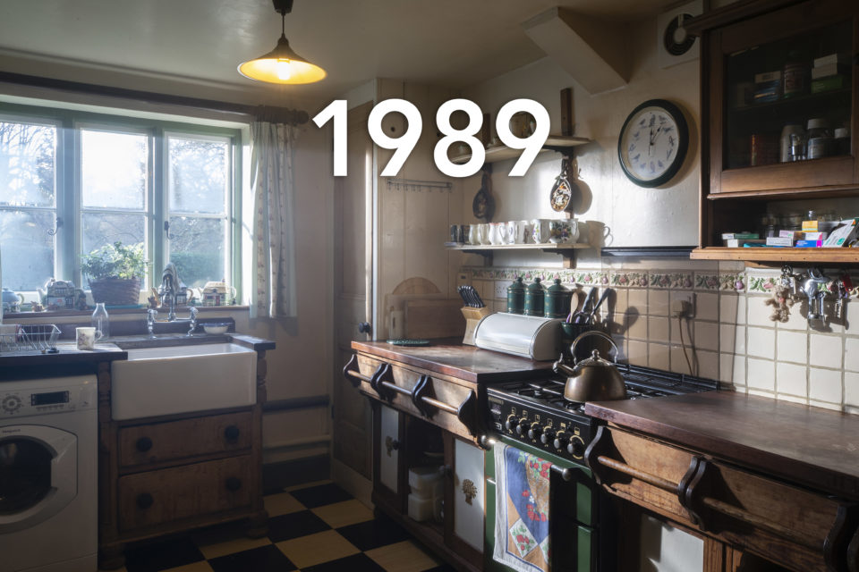 The image shows a country-style kitchen with wooden cupboards and sunken farmhouse sink. A copper kettle sits on top of the cooker and soft lighting comes in through the window, the date 1989 is written over the image.