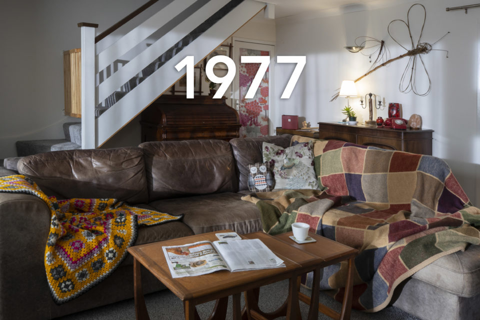 A leather corner sofa is decorated with throws and scatter cushions. In the foreground, a tea cup and a magazine sit on a coffee table. In the background, a metallic dragonfly ornament hangs on the wall, the date 1977 is written over the image.