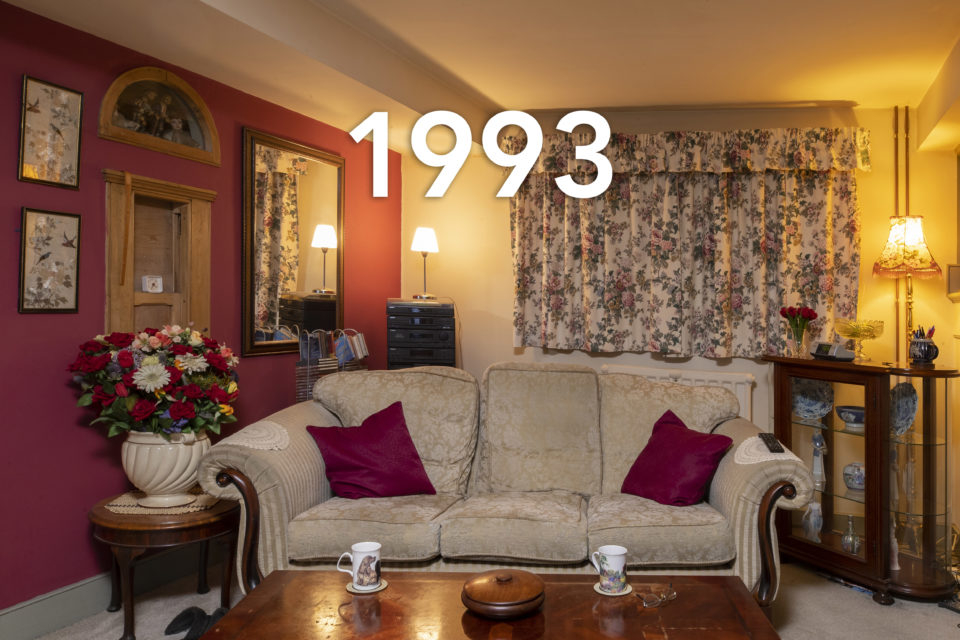 The image shows a homely feeling living room at night. The floral curtains match the huge vase of flowers which sits next to the white sofa. Red cushions decorate the sofa and two cups of tea are placed on the coffee table in the foreground. The date 1993 is written over the image.