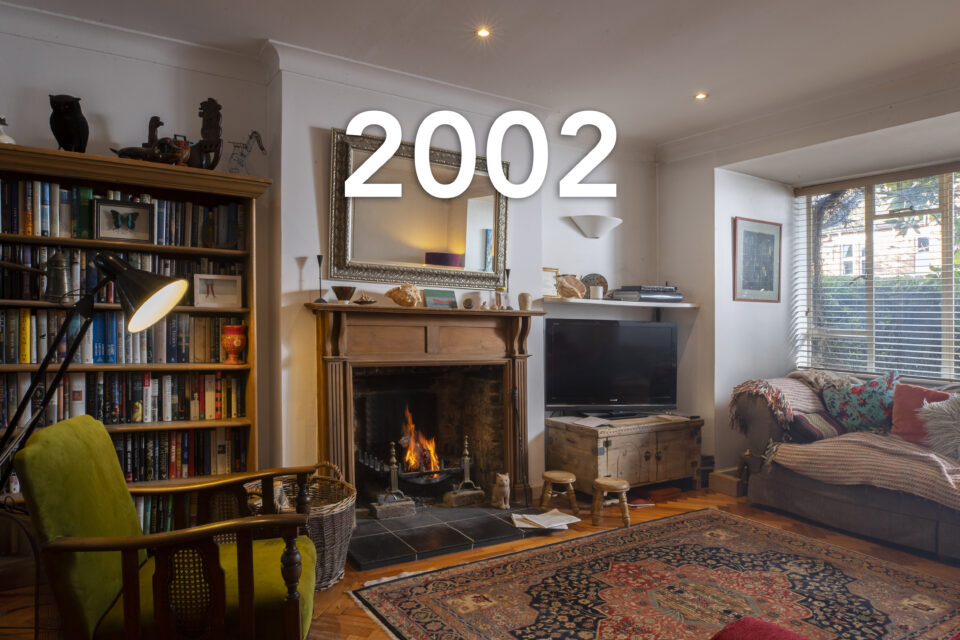 An open fireplace is lit in a family's white living room. A bookcase sits on the right and a TV is to the left. An armchair looks out across the room and a deep sofa is opposite. The date 2002 is written over the image.