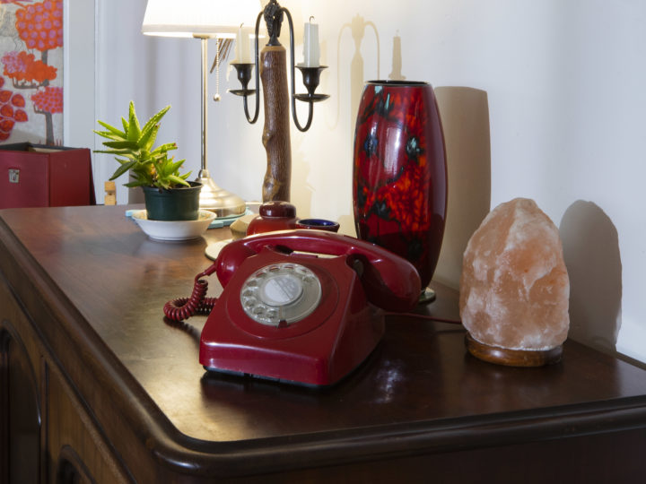 photographs of a red bakelite telephone sitting on a sideboard next to: a lamp, a candle holder, a vase and a salt light.