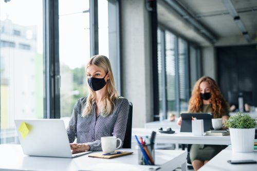 women in office wearing black face masks